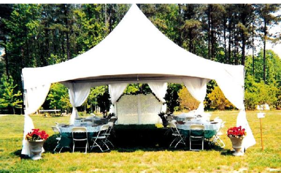 A white 20x20 frame tent placed in garden with white leg skirts and a 10x10 attached to it