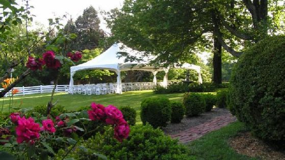 A 20x30 White tent staked in the ground to be used as a ceremony tent. It has white leg skirts and white chair under it