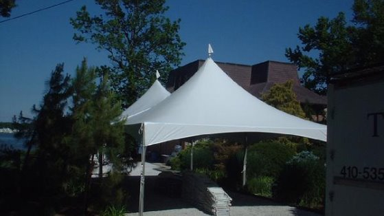 A 20x40 white tent over a driveway and secured by weights