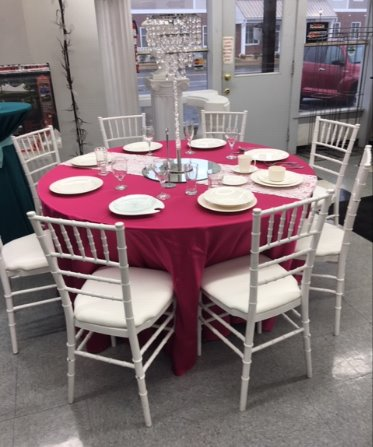 A five foot rount table with floor length hot pink linen showing 8 white chivari chairs around it.  It also is set with white dishes and silverware to show how 8 guests would fit at the table