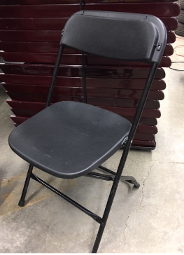 A folding chair with a black metal frame and black plastic seat and back