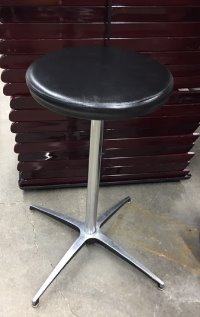 A round seat covered in black leather sitting on a single pole which is attached to a four prong foot