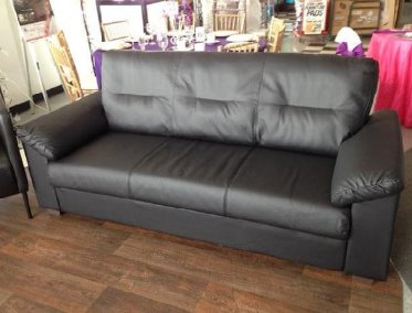 Stuffed black leather sofa with tuft back and overstuffed arms.  It has metal legs