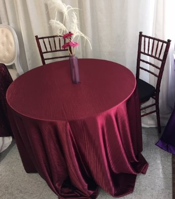 a 3 foot round table with floor length burgundy dupioni linen and mahogany chivari chairs. Can be used as a sweetheart table or table for cake