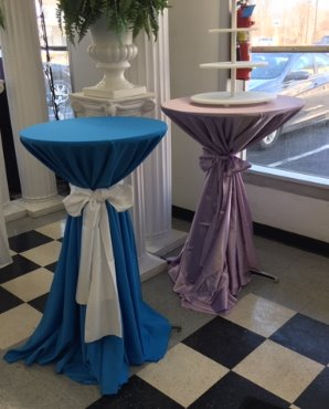 "24"" and 30"" cocktail tables with linens tied to create a hour glass look"