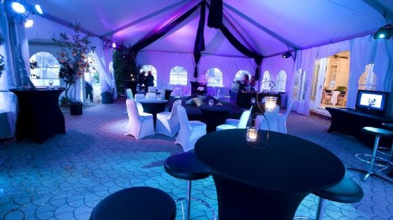 30x70 Frame tent set over a patio with purple up lighting and spandex linens