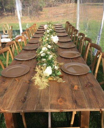 Two farm tables together to create one long table for guest seating at cross back chairs
