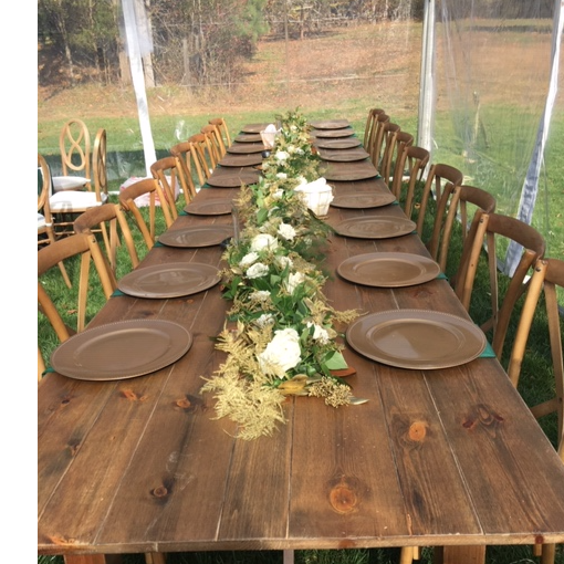 A wooden farm table with gold charger plates, flowers down the center and cross back chairs pulled up to the table