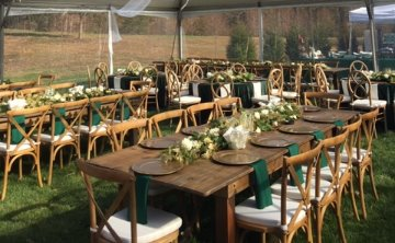 showing seating for guests with farm tables and chairs set up under a clear top tent