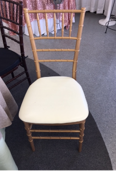 A gold chivari chair with an ivory cushion in our showroom