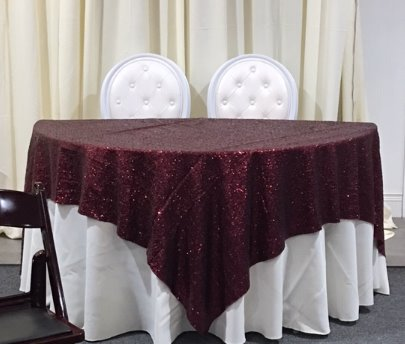 Linens over a 5' round half table used for a sweetheart table at weddings or parties.