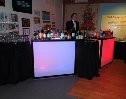 2 light up bars with tables in between to hold the glassware and liquor which create one large bar area and bar tender standing behind. One bar is red and the other is lit blue, but the colors keep changing