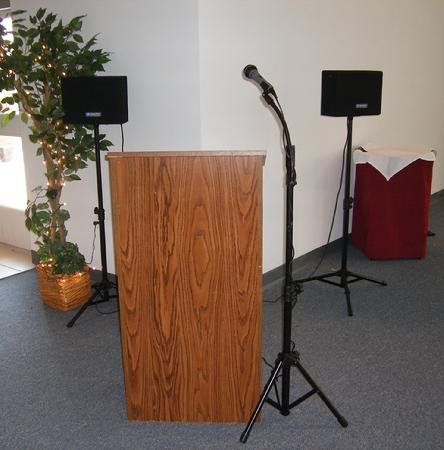 Walnut podium with 2 speaker stands behind it and a microphone next to it on a stand