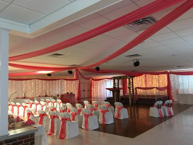 Ceiling draped with coral fabric and the walls are lined with white drape that have twinkle lights behind them and coral drape scalloped on top.  Also showing ceremony chairs with chair covers and coral chair sashes.
