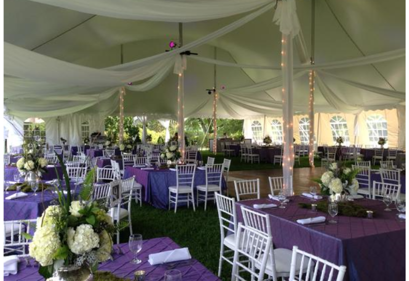 5 foot square tables with purple linens and white chivari chairs set up under a tent. White fabric is hung in streams across tent and twinkle lights are wrapped around tent poles covered in lightweight white fabric