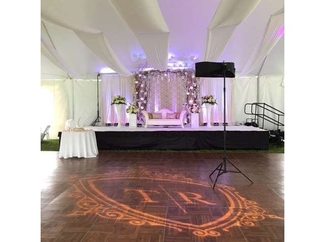Parquet dance floor with a gobo light showing a monogram and a stage in the background
