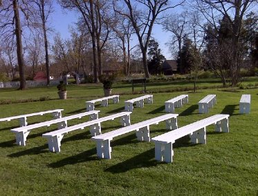 White 10 foot long bench set up on grass for a wedding ceremony