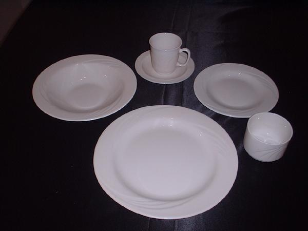 A place setting of white dishes with white cup and saucer and a bouillon cup