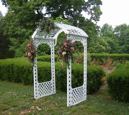 A white lattice wedding arch decorated with bouquets of pink and cream flowers