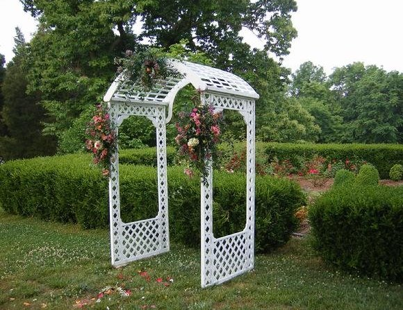 Picture of a white lattice arch decorated with wedding flowers