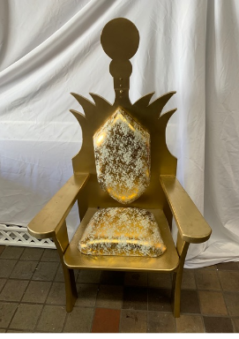 A oversized heavy wooden chair that has a back that is shaped with points shooting out and a round circle on top. It has gold and white fabric that is padded and covers part of seat and back
